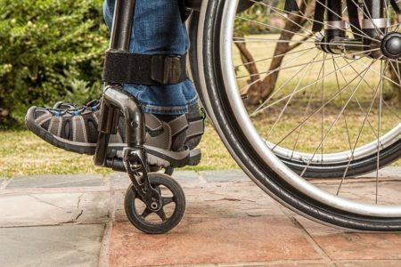 Zdjęcie przedstawia zbliżenie na wózek inwalidzki na którym ktoś siedzi, widać koło wózka i stopy osoby na wózku.